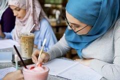 Amis islamiques discutant et livres de lecture ensemble Photographie stock libre de droits
