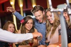 Amis ivres observant le cocktail de versement de barman Photos stock