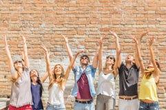 Amis jetant des confettis dans le ciel Photos libres de droits