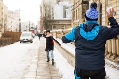 Amis jetant des flocons de neige à l'un l'autre Photographie stock
