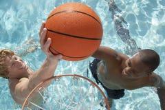 Amis jouant au basket-ball de l'eau dans la piscine Image libre de droits