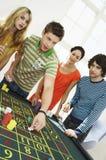 Amis jouant au Tableau de roulette Photographie stock libre de droits