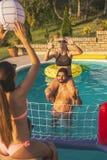Amis jouant au volleyball dans une piscine photographie stock libre de droits