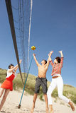 Amis jouant au volleyball sur la plage Photo stock