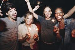 Amis jouant avec des cierges magiques et la célébration Photo stock