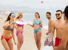 Amis jouant avec des raquettes à la plage Photo stock