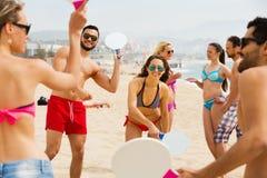 Amis jouant avec des raquettes à la plage Photos libres de droits