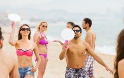 Amis jouant avec des raquettes à la plage Photographie stock