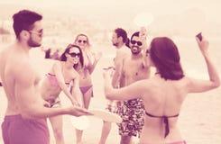 Amis jouant avec des raquettes à la plage Images libres de droits