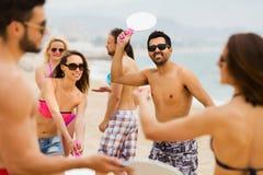 Amis jouant avec des raquettes à la plage Photographie stock libre de droits