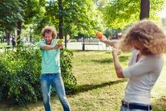 Amis jouant avec l'arme à feu d'eau Images stock