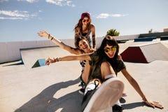 Amis jouant avec la planche à roulettes au parc de patin Photographie stock libre de droits