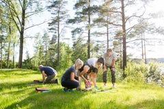 Amis jouant avec les blocs constitutifs sur le champ herbeux image libre de droits