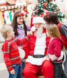 Amis jouant avec Santa Claus Photos stock
