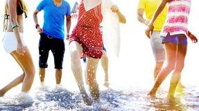Amis jouant dans l'eau à une plage Photos libres de droits