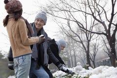 Amis jouant dans la neige, riant Photo stock