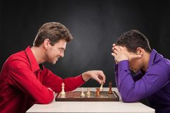 Amis jouant des échecs sur le fond noir Photo stock