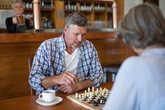 Amis jouant des échecs tout en ayant le café Images libres de droits