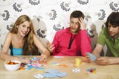 Amis jouant des cartes comme victoires de femme Photos stock