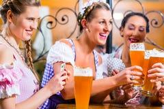 Amis jouant des cartes en bière potable d'auberge ou de bar Photographie stock