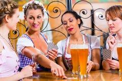 Amis jouant des cartes en bière potable d'auberge ou de bar Images stock