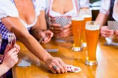 Amis jouant des cartes en bière potable de bar Photos libres de droits