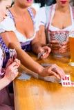 Amis jouant des cartes en bière potable de bar Photos stock