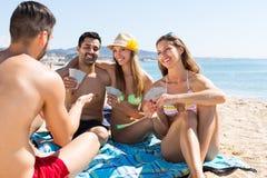 Amis jouant des cartes sur la plage Image libre de droits