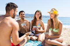 Amis jouant des cartes sur la plage Photo libre de droits