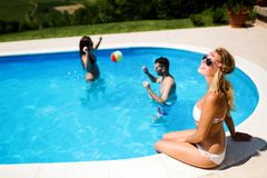 Amis jouant des jeux de boule dans la piscine Image stock