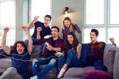Amis jouant des jeux vidéo dans la chambre Photos libres de droits