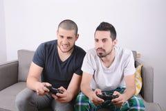Amis jouant des jeux vidéo sur le divan Image stock