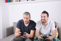 Amis jouant des jeux vidéo sur le divan Images libres de droits