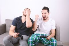 Amis jouant des jeux vidéo sur le divan Photos libres de droits