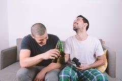 Amis jouant des jeux vidéo sur le divan Photo libre de droits