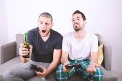 Amis jouant des jeux vidéo sur le divan Images stock