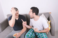Amis jouant des jeux vidéo sur le divan Image libre de droits