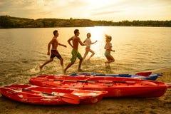 Amis jouant et ayant l'amusement dans l'eau sur la plage près des kayaks sous le ciel dramatique de soirée au coucher du soleil Images stock