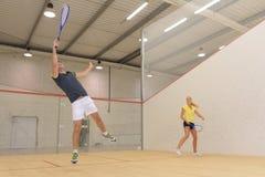 Amis jouant l'indoori de jeu de tennis dans le court de tennis photos stock