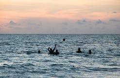 Amis jouant la boule dans l'océan au crépuscule Photo stock
