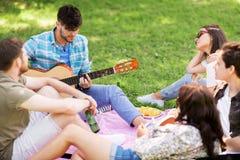 Amis jouant la guitare au pique-nique en parc d'été Photo libre de droits