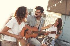 Amis jouant la guitare et le chant Photos libres de droits