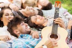 Amis jouant la guitare et refroidissant sur la couverture Photo stock
