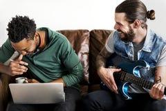 Amis jouant la musique ensemble sur le divan Photos stock