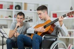 Amis jouant la musique une dans le fauteuil roulant Image libre de droits