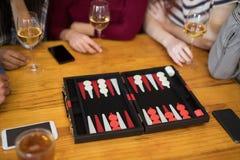 Amis jouant le backgammon tout en ayant le verre de vin Photographie stock