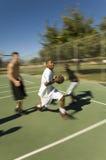 Amis jouant le basket-ball sur la cour Image libre de droits