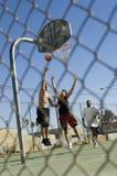 Amis jouant le basket-ball sur la cour Photographie stock libre de droits