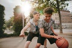 Amis jouant le basket-ball sur la cour extérieure Photographie stock libre de droits