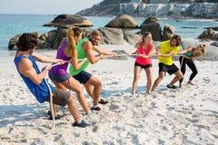 Amis jouant le conflit sur le rivage à la plage Photographie stock libre de droits